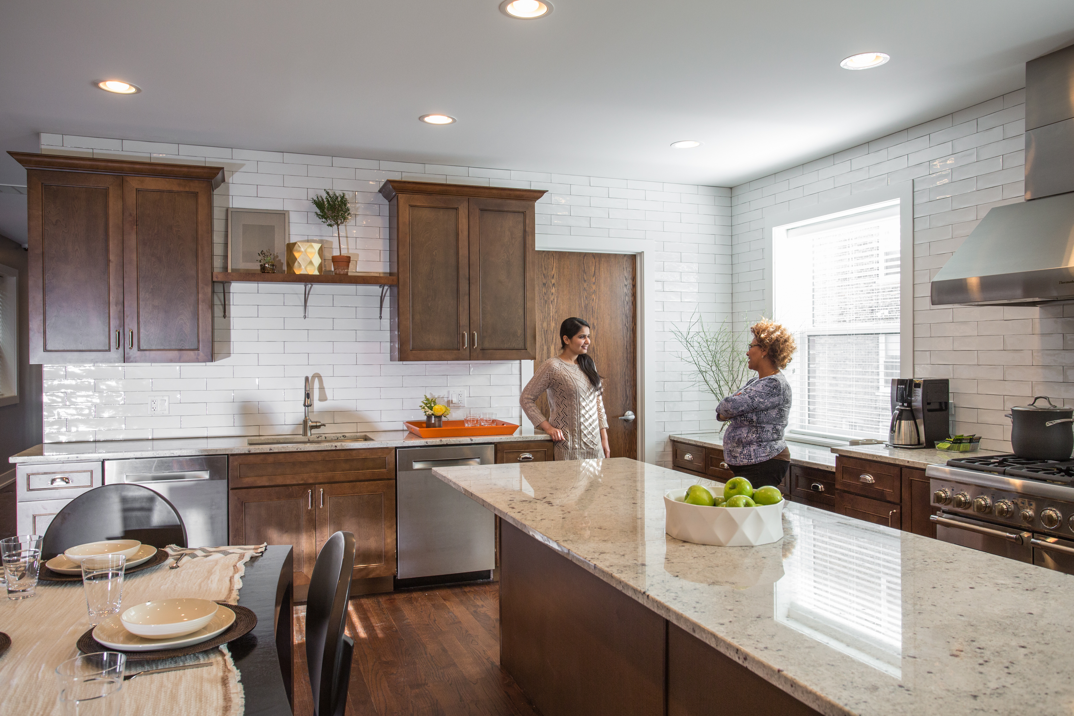Two people talking in a kitchen
