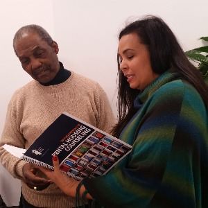 Two people looking over a book together at a training